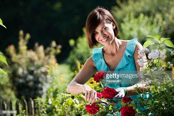 Germany, Bavaria, Woman pruning flowers in garden, smiling, portrait
