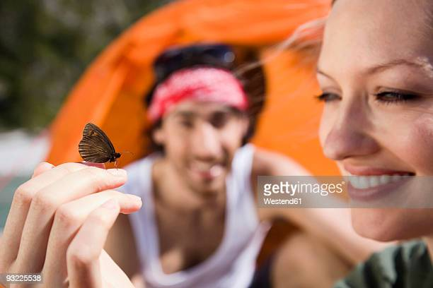 Germany, Bavaria, Butterfly resting on woman's hand, man in background