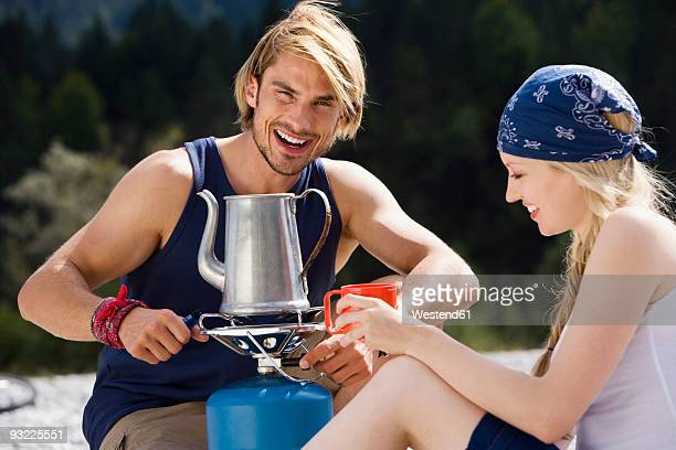 Germany, Bavaria, Young couple camping, smiling