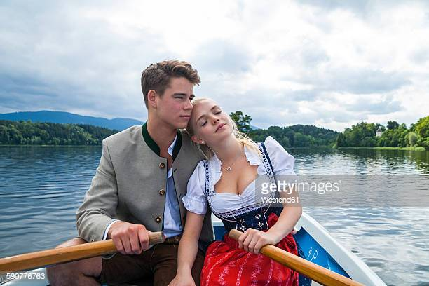 germany, bavaria, young couple in love wearing traditional clothes sitting in a rowing boat on staffelsee - teen cleavage stock photos and pictures