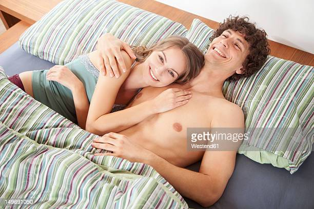 Germany, Bavaria, Young couple on bed, smiling