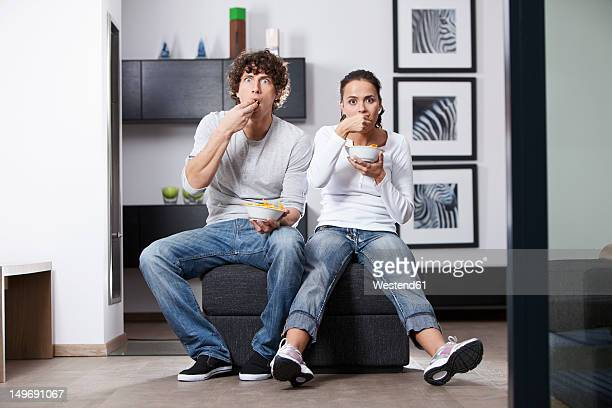 germany, bavaria, young couple watching tv - man eating woman out - fotografias e filmes do acervo