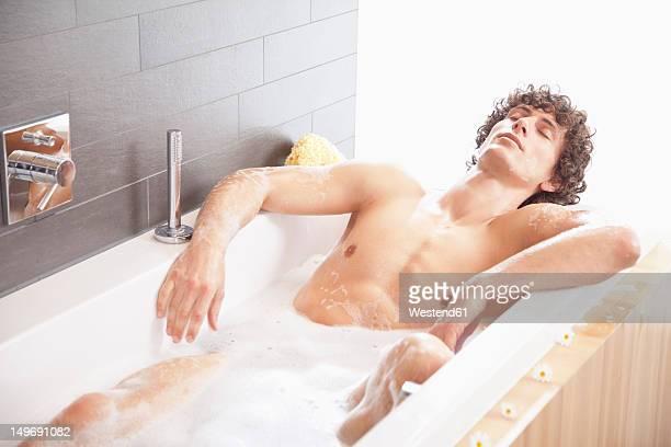 Germany, Bavaria, Young man having bath in bathtub