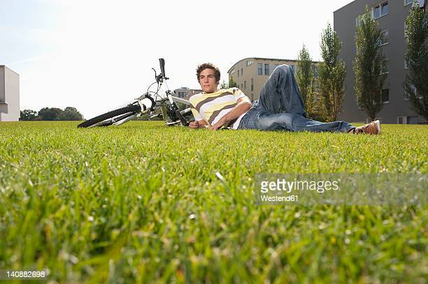 Germany, Bavaria, Young man lying in grass