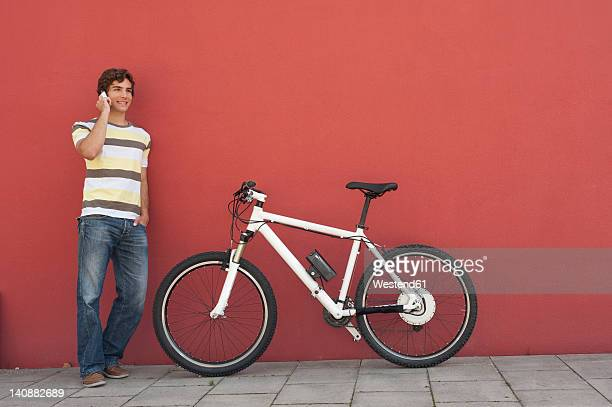 Germany, Bavaria, Young man on phone against red background, smiling