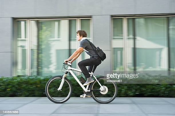 Germany, Bavaria, Young man riding bicycle