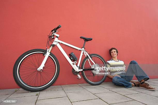 Germany, Bavaria, Young man sitting besides bicycle, smiling
