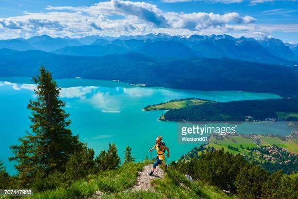 Germany, Bavaria, Young woman jogging at Lake Walchensee