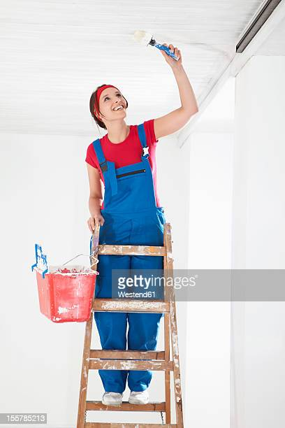 Germany, Bavaria, Young woman painting ceiling