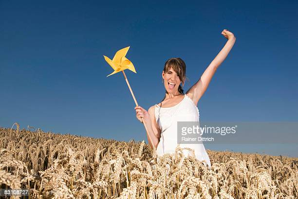 Germany, Bavaria, young woman standing in field holding pinwheel, cheering, portrait