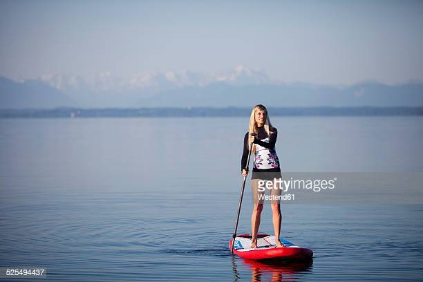 Germany, Bavaria, young woman standing on stand up paddle board at Lake Starnberg