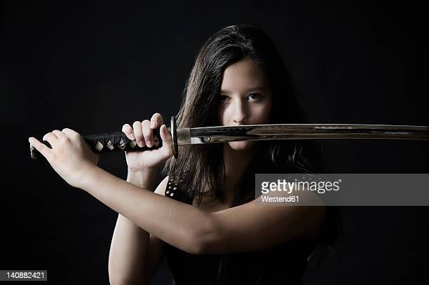 Germany, Bavaria, Young woman with sword against black background, portrait