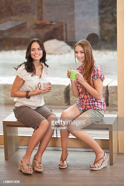 Germany, Bavaria, Young women sitting on bench with cup, smiling