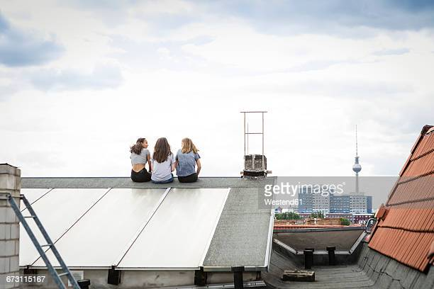 Germany, Berlin, back view of three friends sitting side by side on roof top