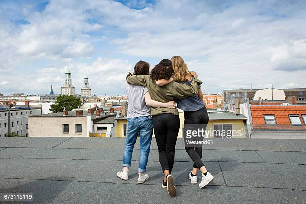 Germany, Berlin, back view of three teenage girls standing arm in arm on roof top