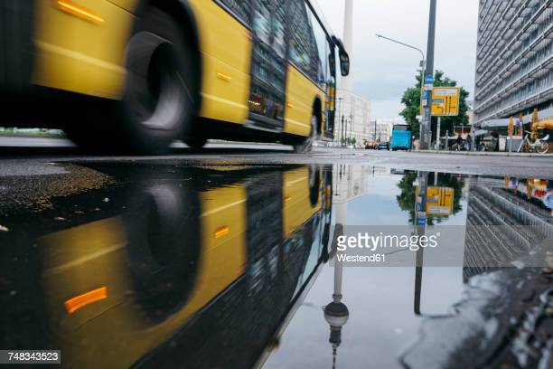 germany, berlin, berlin tv tower reflecting in puddle after rain - bus stock-fotos und bilder