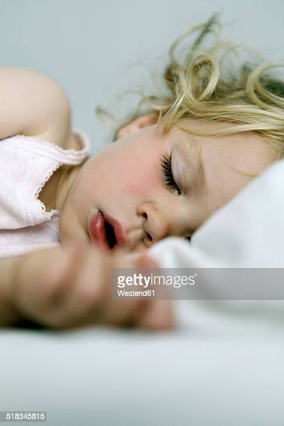 germany, berlin, blond girl sleeping - girls open mouth stockfoto's en -beelden