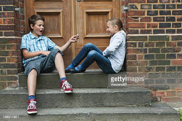Germany, Berlin, Boy and girl sitting at entrance door