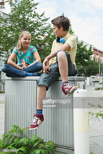 Germany, Berlin, Boy and girl sitting on wall