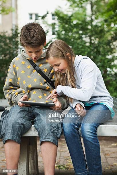 Germany, Berlin, Boy and girl using digital tablet