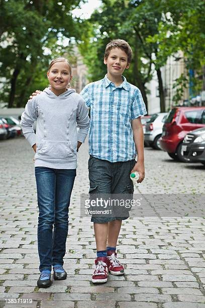 Germany, Berlin, Boy and girl walking in street as couple