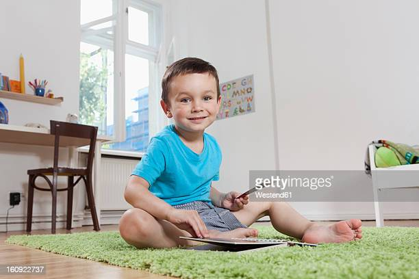germany, berlin, boy sitting on floor with book, smiling, portrait - nur jungen stock-fotos und bilder