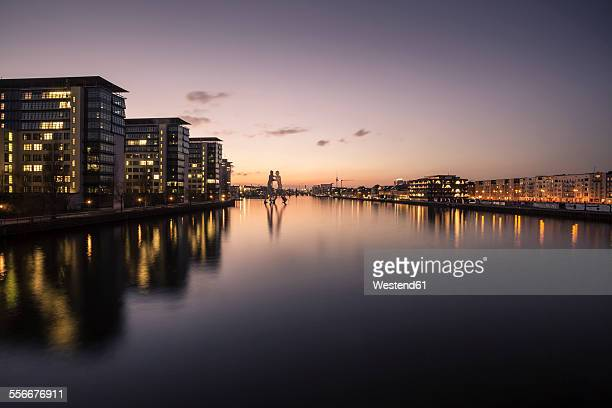 Germany, Berlin, buildings and Molecule Man at River Spree in the evening