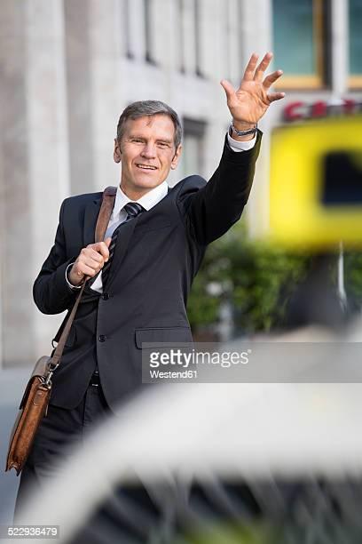 Germany, Berlin, Businessman hailing taxi