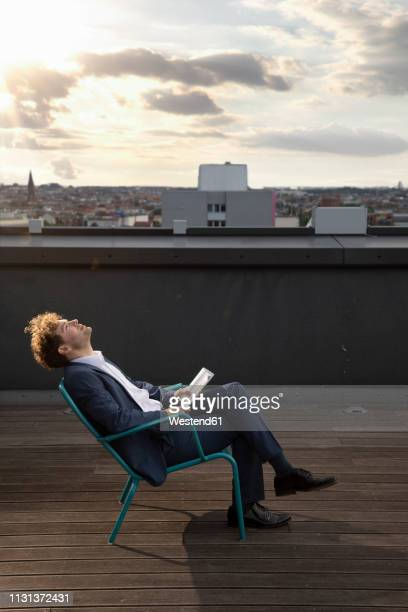 Germany, Berlin, businessman relaxing on roof terrace at sunset