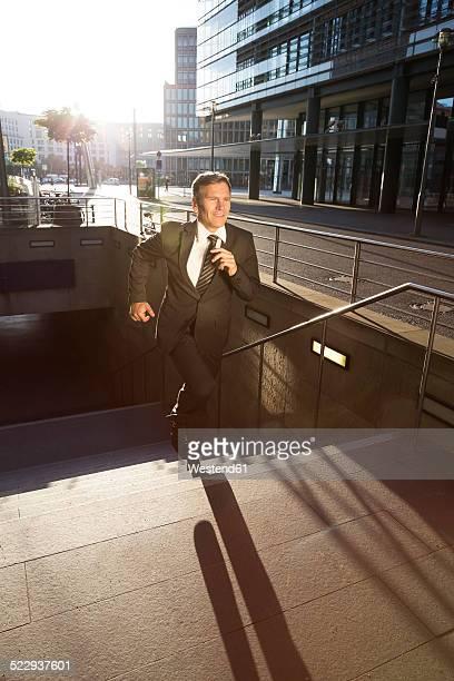 Germany, Berlin, Businessman running on stairs
