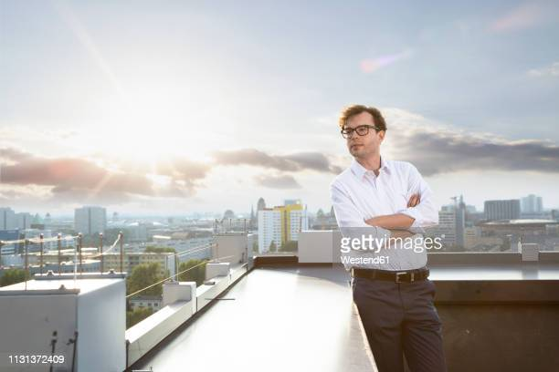 germany, berlin, businessman standing on roof terrace looking at distance in the evening - un solo hombre fotografías e imágenes de stock
