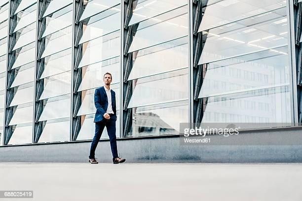 germany, berlin, businessman walking at potsdamer platz - architektur stock-fotos und bilder