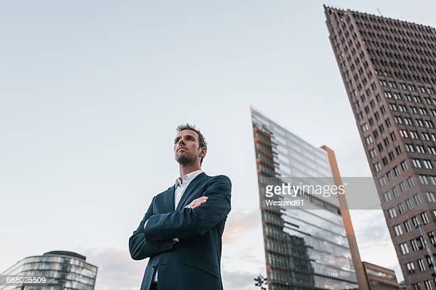 germany, berlin, businessman with arms crossed standing at potsdamer platz - vista de ângulo baixo - fotografias e filmes do acervo