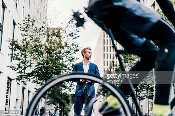 Germany, Berlin, businessman with cyclist passing by in the foreground