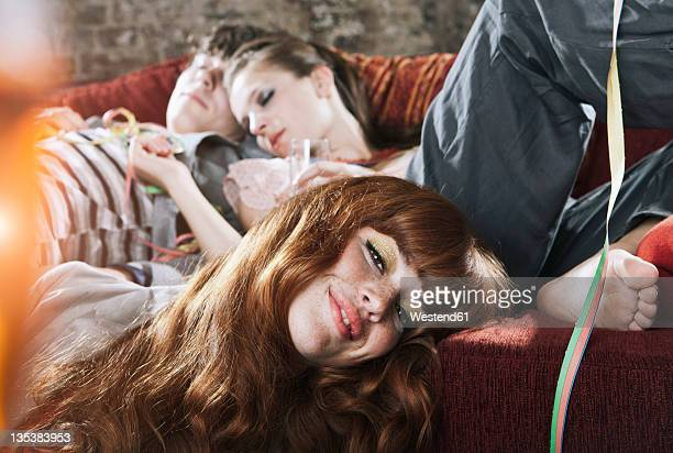germany, berlin, close up of young man and women relaxing on couch after party - after party stockfoto's en -beelden