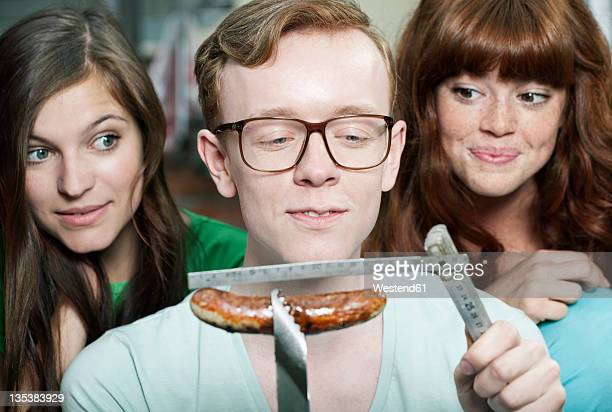 Germany, Berlin, Close up of young man measuring grilled sausage and women beside him, smiling