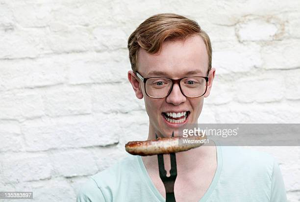 Germany, Berlin, Close up of young man with grilled sausage, smiling