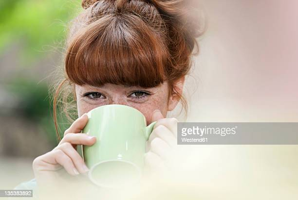 Germany, Berlin, Close up of young woman drinking coffee, smiling, portrait