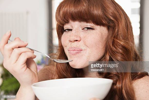 Germany, Berlin, Close up of young woman eating cereals, smiling, portrait