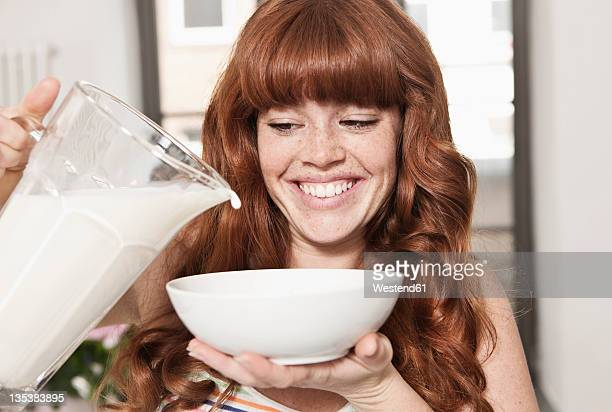 germany, berlin, close up of young woman preparing cereals, smiling - fülle stock-fotos und bilder