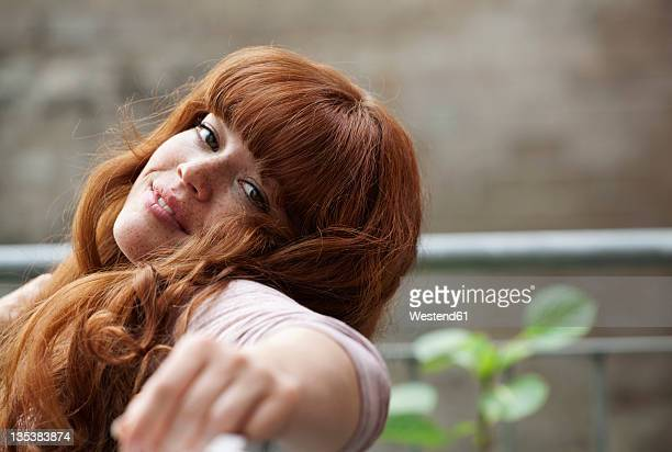 germany, berlin, close up of young woman sitting on bench, smiling, portrait - freckle stock photos and pictures