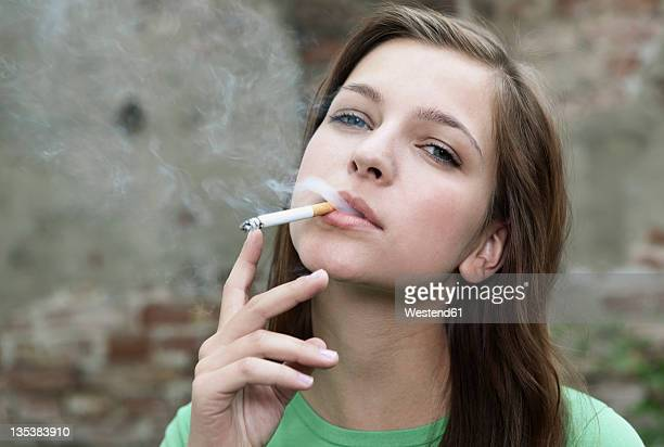 germany, berlin, close up of young woman smoking, portrait - femme qui fume photos et images de collection