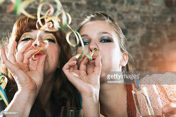 Germany, Berlin, Close up of young women blowing party streamers