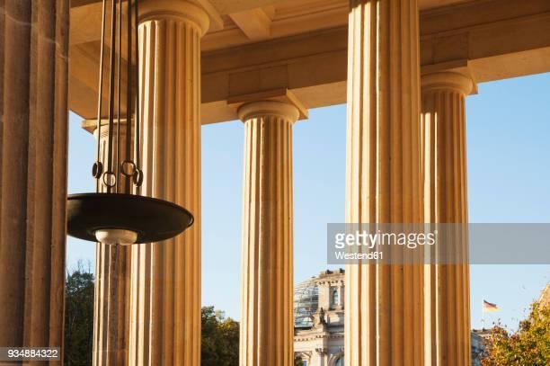 germany, berlin, columns of brandenburger tor, reichstag building in background - porta cittadina foto e immagini stock