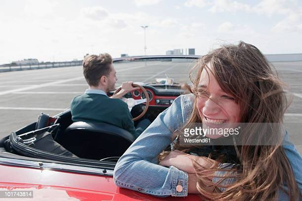 Germany, Berlin, Couple driving in cabriolet, smiling, portrait