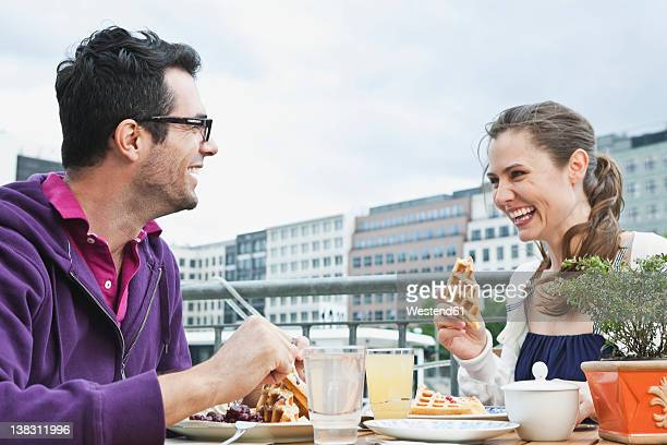Germany, Berlin, Couple eating food at cafe