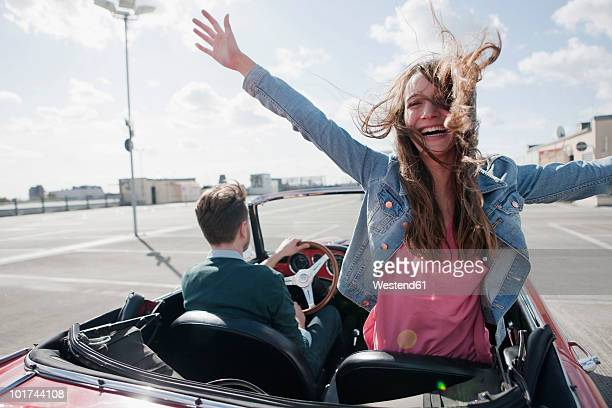 Germany, Berlin, Couple in cabriolet, woman with arms outstretched