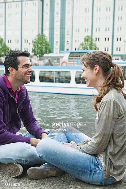 Germany, Berlin, Couple sitting face to face on riverbank
