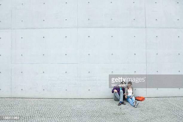 germany, berlin, couple using laptop on stairway - big white women stock photos and pictures