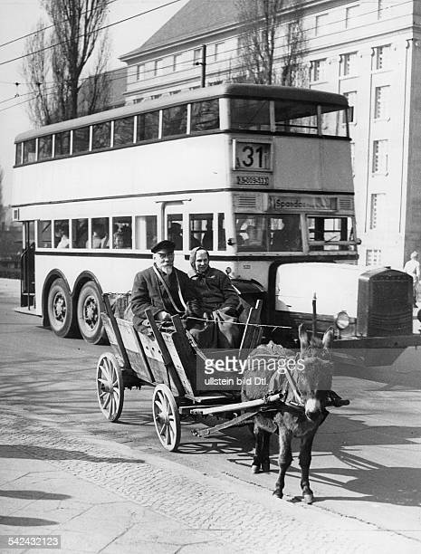 Germany Berlin elderly couple in a donkey cart in front of a doubledecker bus in Spandau 1953